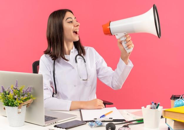 Jonge vrouwelijke arts in witte jas met een stethoscoop om haar nek schreeuwen naar megafoon blij en opgewonden zittend aan tafel met laptop over roze muur