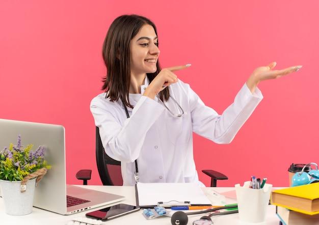 Jonge vrouwelijke arts in witte jas met een stethoscoop om haar nek wijzend met de vinger naar de zijkant presenteren met arm van haar hand glimlachend zittend aan tafel met laptop over roze muur