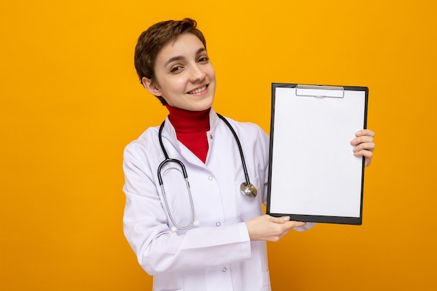 Jonge vrouwelijke arts in witte jas met stethoscoop die klembord vasthoudt met blanco pagina's die er gelukkig en positief uitzien en vrolijk glimlachen