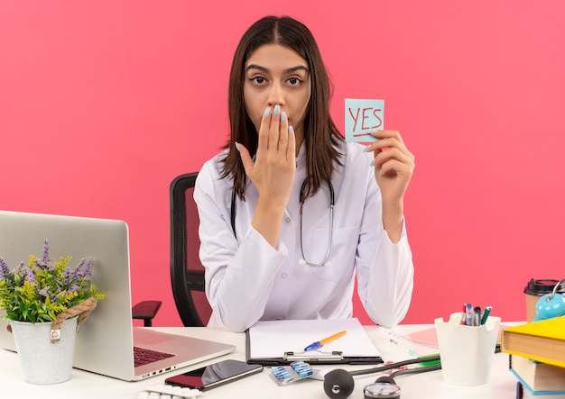 Jonge vrouwelijke arts in witte jas met stethoscoop om haar nek die herinneringspapier met woord vasthoudt ja op zoek verrast die mond bedekt met hand zittend aan tafel met laptop over roze muur