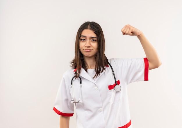 Jonge vrouwelijke arts in witte jas met stethoscoop om haar nek gebalde vuist hand opsteken op zoek zelfverzekerd, winnaar concept staande over witte muur