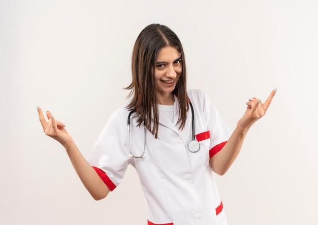 Jonge vrouwelijke arts in witte jas met stethoscoop om haar nek kijkend naar de voorkant glimlachend vrolijk makend rotssymbool met beide handen staande over witte muur