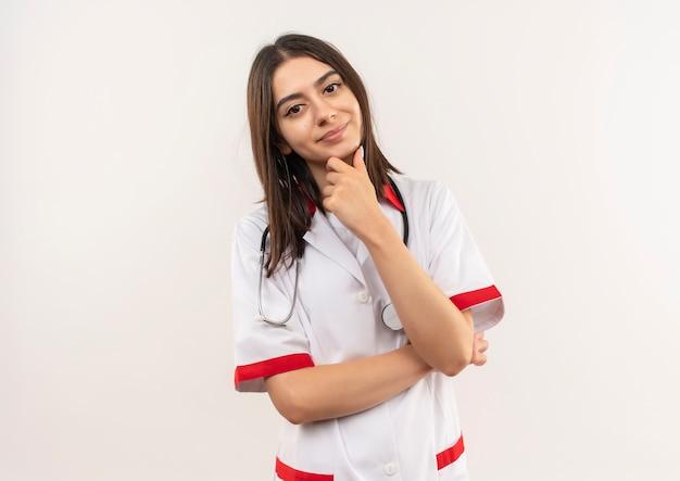 Jonge vrouwelijke arts in witte jas met stethoscoop om haar nek naar voren kijkend met hand op kin op zoek zelfverzekerd denken staande over witte muur