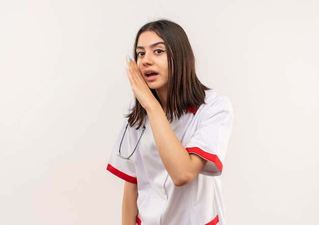 Jonge vrouwelijke arts in witte laag met stethoscoop om haar hals die een geheim met hand dichtbij mond vertelt die zich over witte muur bevindt