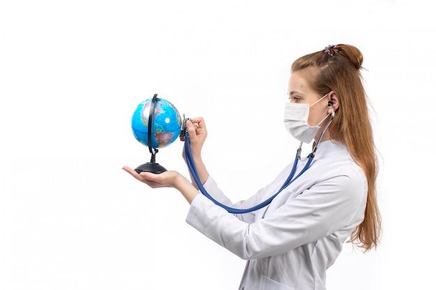 Jonge vrouwelijke arts in witte medische pak met stethoscoop in wit beschermend masker luisteren naar de kleine wereldbol op de witte