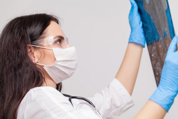 Jonge vrouwelijke arts kijken naar de x-ray foto in het ziekenhuis