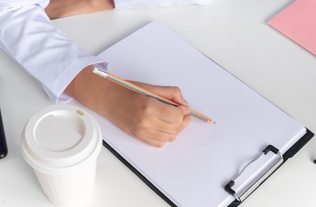 Jonge vrouwelijke arts met een medisch gewaad met een stethoscoop en een bril zit aan tafel met medische hulpmiddelen - geïsoleerd op blauwe achtergrond