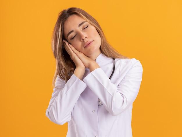 Jonge vrouwelijke arts met gesloten ogen die een medisch gewaad draagt met een stethoscoop die een slaapgebaar toont dat op een gele muur is geïsoleerd