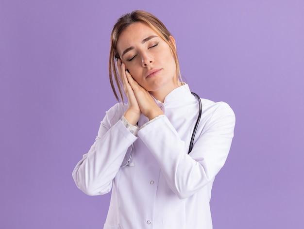 Jonge vrouwelijke arts met gesloten ogen die medisch kleed met stethoscoop dragen dat slaapgebaar toont dat op purpere muur wordt geïsoleerd
