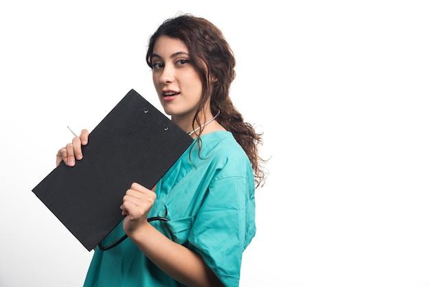Jonge vrouwelijke arts met het klembord van de stethoscoopholding in eenvormig op witte achtergrond