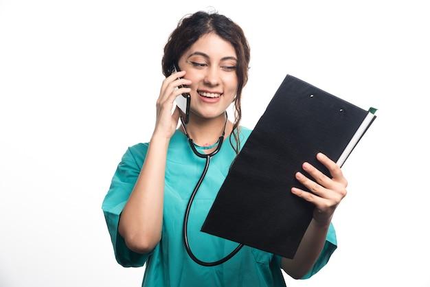 Jonge vrouwelijke arts met klembord en praten over de mobiele telefoon op witte achtergrond
