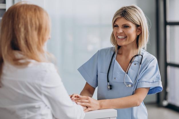 Jonge vrouwelijke arts met patiënt bij kliniek