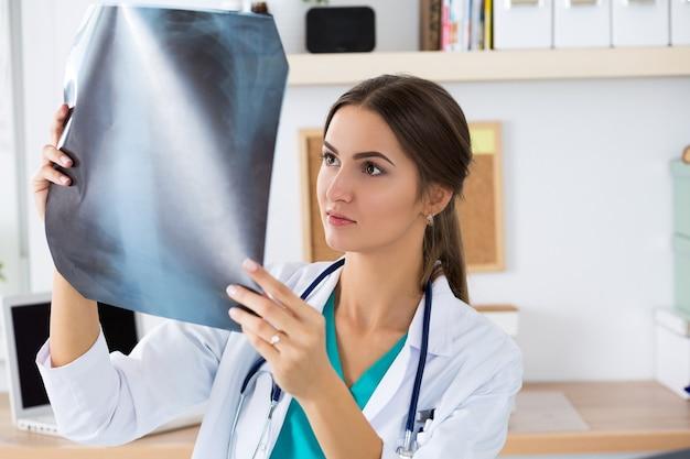 Jonge vrouwelijke arts of stagiair kijken naar longen x ray afbeelding staande op haar kantoor. radiologie, gezondheidszorg, medische dienst of onderwijsconcept.