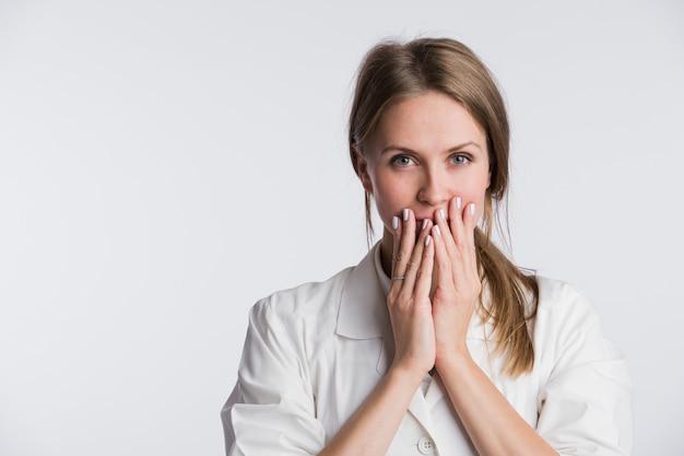 Jonge vrouwelijke arts of verpleegkundige is geschokt met de handen op haar mond