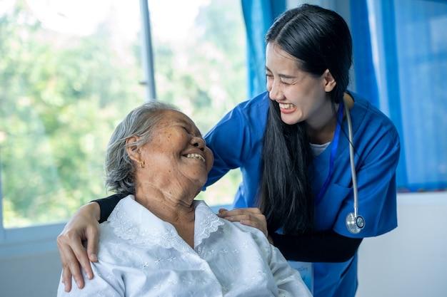 Jonge vrouwelijke arts of verpleegster helpt bij het verzorgen en helpt bij het ondersteunen van oude damepatiënt in het ziekenhuis, ouderenzorgconcept voor geriatrie.