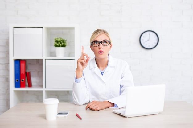 Jonge vrouwelijke arts of wetenschapper die ideeteken in bureau toont