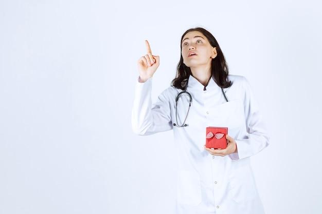 Jonge vrouwelijke arts ondertekent kant terwijl ze haar kleine geschenkdoos in haar linkerhand houdt