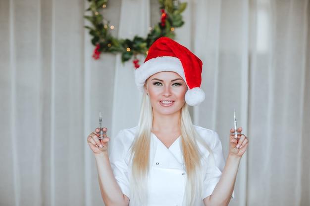 Jonge vrouwelijke arts poseren met spuiten op witte achtergrond met kerstkrans.
