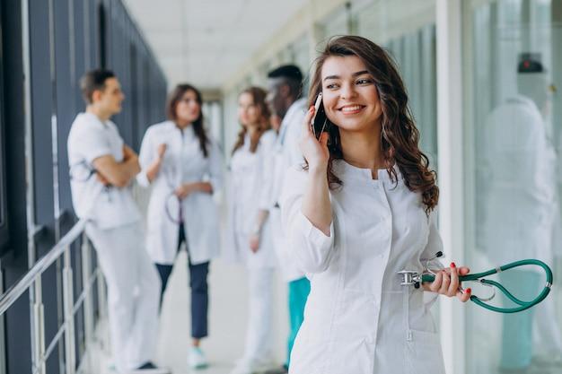 Jonge vrouwelijke arts praten via de telefoon in de gang van het ziekenhuis