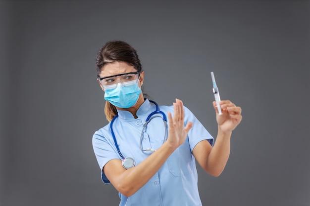 Jonge vrouwelijke arts spuit te houden en gebaren alsof ze tegen vaccinatie is.