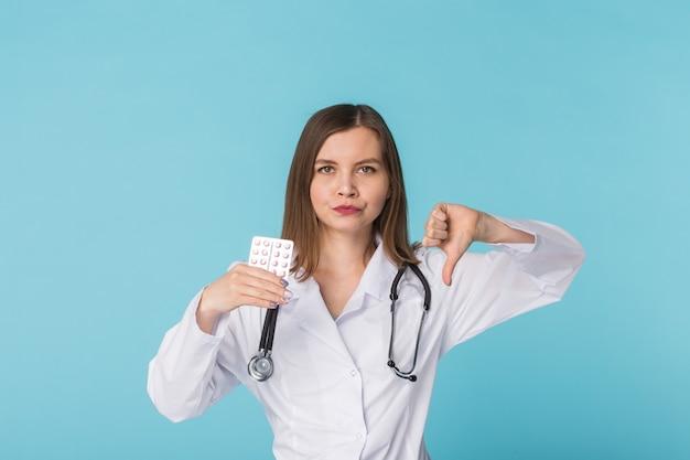 Jonge vrouwelijke arts tegen pakje pillen in studio