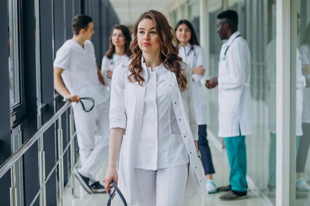 Jonge vrouwelijke arts wandelen door de gang van het ziekenhuis