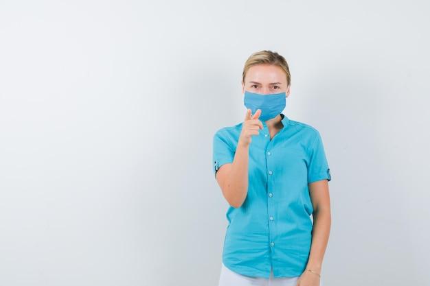 Jonge vrouwelijke arts wijst in medisch uniform, masker en ziet er zelfverzekerd uit