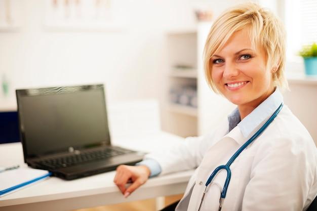 Jonge vrouwelijke arts zit in haar kantoor