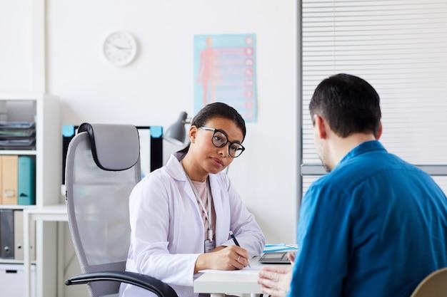 Jonge vrouwelijke arts zittend aan tafel, notities maken en luisteren naar de patiënt tijdens zijn bezoek op kantoor