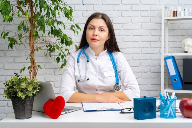 Jonge vrouwelijke artsencardioloog die bij haar bureau en het werken zit
