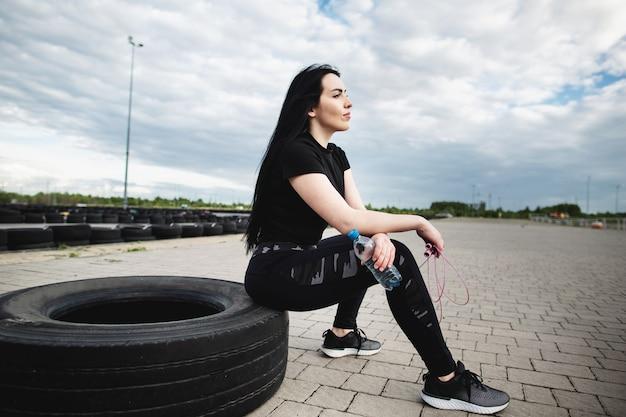 Jonge vrouwelijke atleet die band-tik oefening op de straat doet. vrouw met lang haar in zwarte sportkleding rust na een training zittend op een band. atletische brunette doet oefeningen met krachttraining