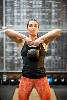 Jonge vrouwelijke atleet die een kettlebellgewicht houdt