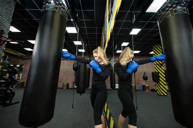 Jonge vrouwelijke atleet in blauwe bokshandschoenen raakt een peer in de ring