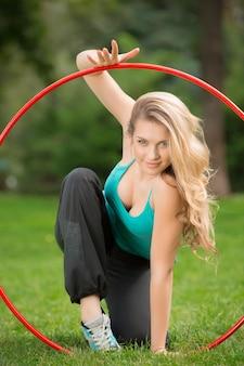 Jonge vrouwelijke atleet met hoelahoep in het park