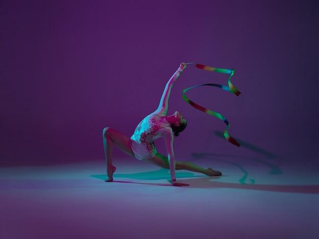 Jonge vrouwelijke atleet, ritmische gymnastiek artiest dansen, training geïsoleerd op paarse studio achtergrond met neon licht. mooi meisje oefenen met apparatuur. genade in prestaties.