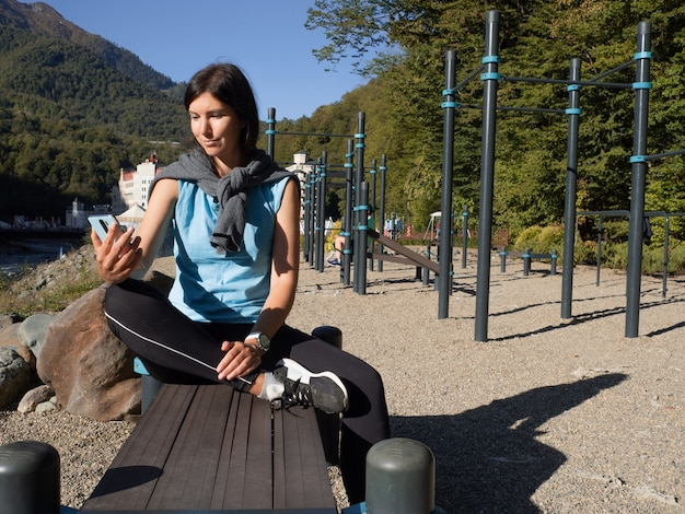Jonge vrouwelijke atleet zit op een buitensportveld