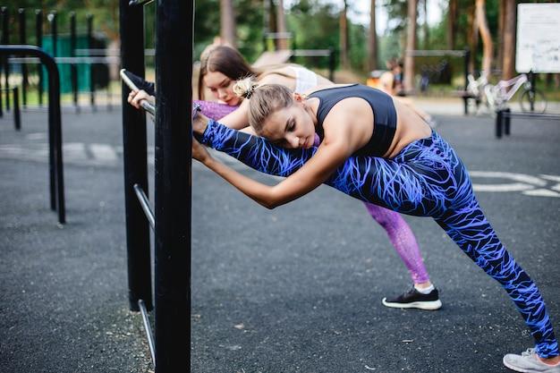 Jonge vrouwelijke atleten die zich vóór het lopen in park uitrekken.