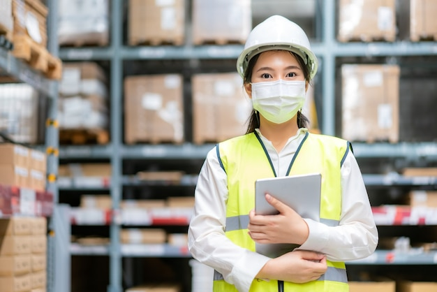 Jonge vrouwelijke auditor of stagiair personeel draagt masker tijdens de covid-pandemie in het magazijn