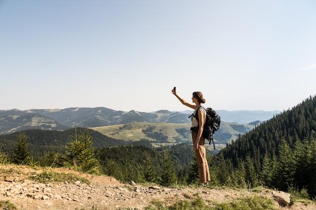 Jonge vrouwelijke backpacker gebruikt mobiele telefoon voor zelfportret in landelijk berggebied van oekraïense karpaten
