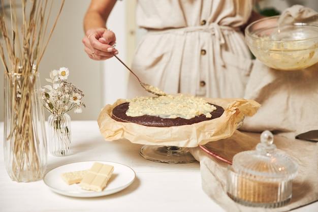 Jonge vrouwelijke bakker die een heerlijke chocoladetaart maakt met room op een witte tafel