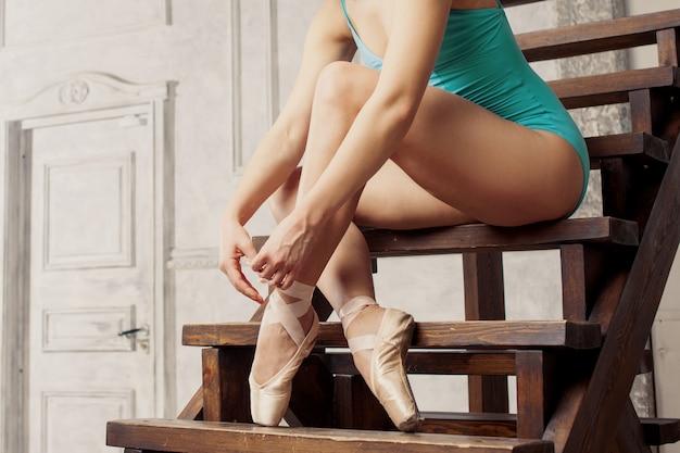 Jonge vrouwelijke balletdanser bindende linten op hun pointe.