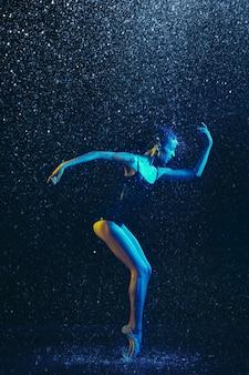 Jonge vrouwelijke balletdanser die onder waterdruppels en spray presteert. kaukasisch model dansen in neonlichten. aantrekkelijke vrouw. ballet en hedendaags choreografieconcept. creatieve kunstfoto.