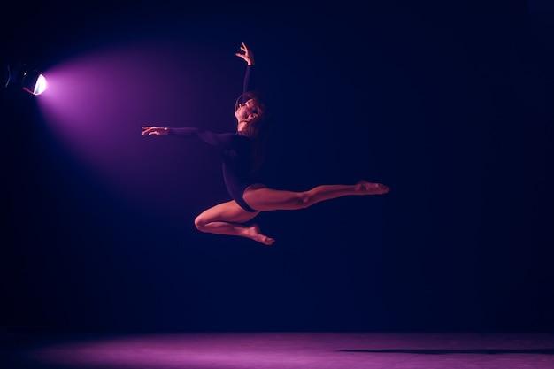 Jonge vrouwelijke balletdanser die op de achtergrond van de neonlichtenstudio danst. ballerinaproject met kaukasisch model. het concept van ballet, dans, kunst, hedendaags choreografie