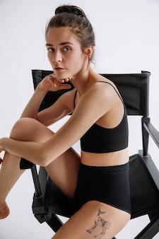 Jonge vrouwelijke balletdanser in zwarte bodysuit tegen witte studiomuur