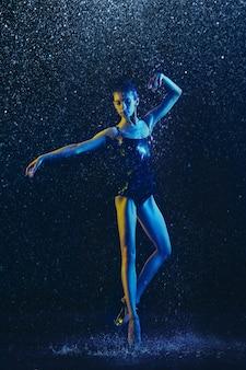 Jonge vrouwelijke balletdanser presteren onder waterdruppels en spray. kaukasisch model dansen in neonlichten. aantrekkelijke vrouw. ballet en hedendaags choreografieconcept. creatieve kunstfoto.
