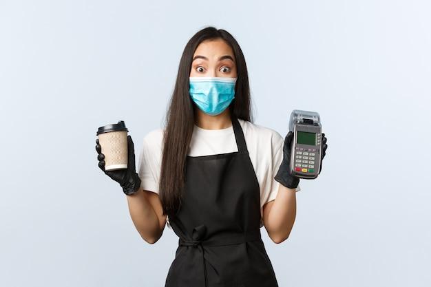 Jonge vrouwelijke barista die beschermend masker draagt dat een koffie houdt
