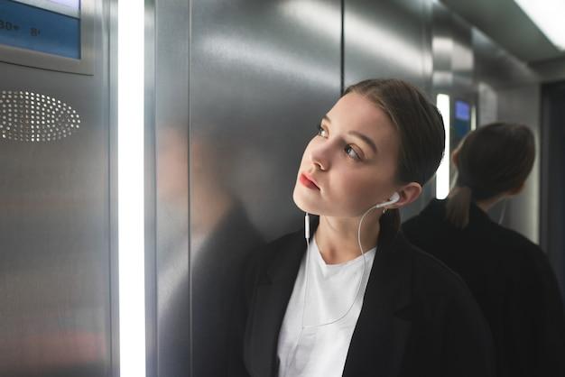 Jonge vrouwelijke beambte staat in de lift en luistert naar muziek in de koptelefoon