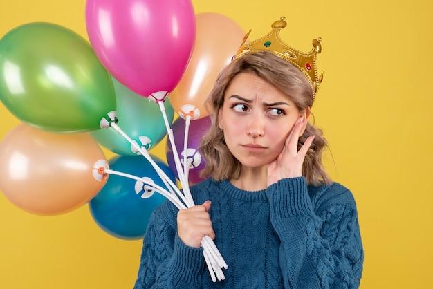 Jonge vrouwelijke bedrijf ballonnen in kroon op geel