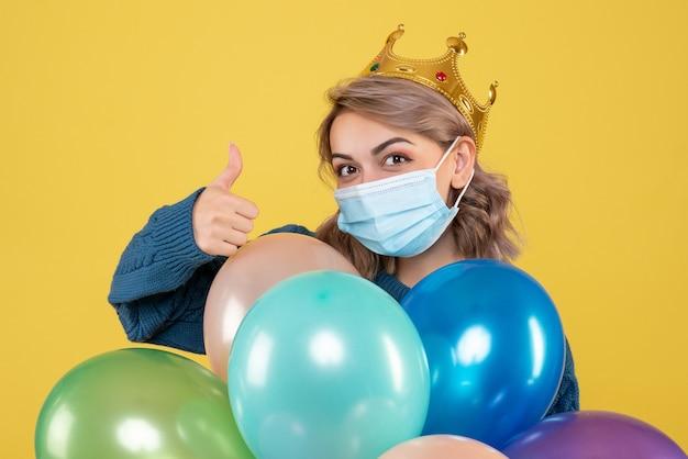 Jonge vrouwelijke bedrijf ballonnen in steriel masker op geel