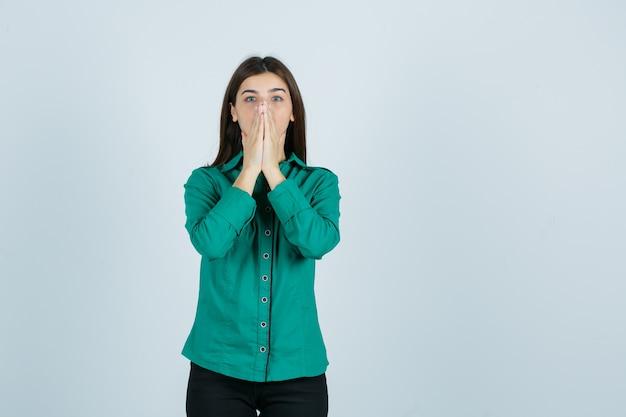 Jonge vrouwelijke bedrijf geklemd handen over gezicht in groen shirt en op zoek angstig. vooraanzicht.
